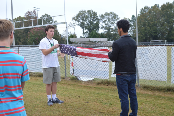 Joseph Suddeth and Justin Anderson folding American flag during Veterans Day ceremony