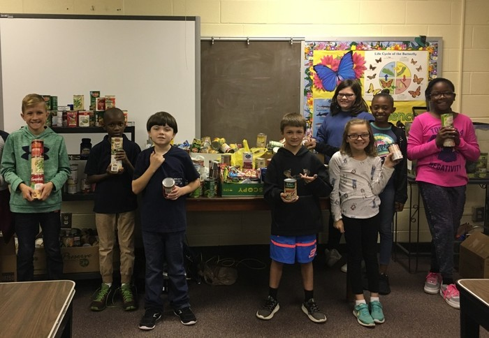 Westwood Elementary students holding cans from can drive fundraiser