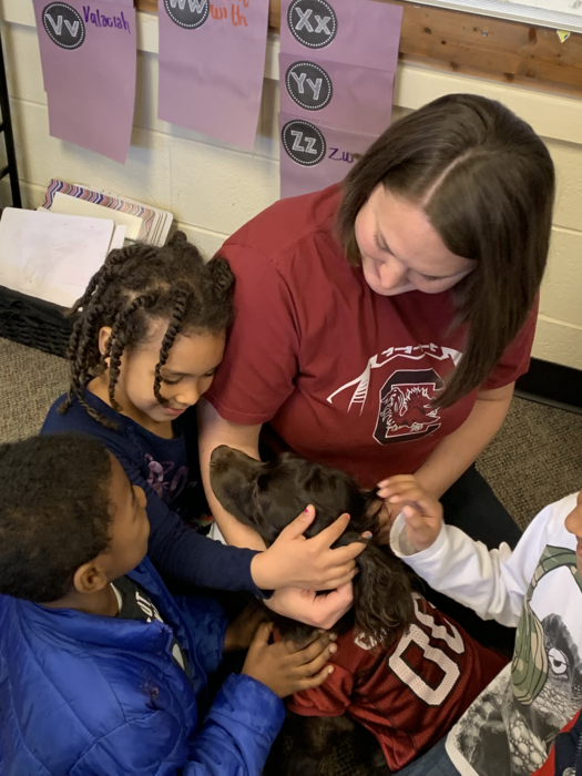 Coach Newton share her dog with students