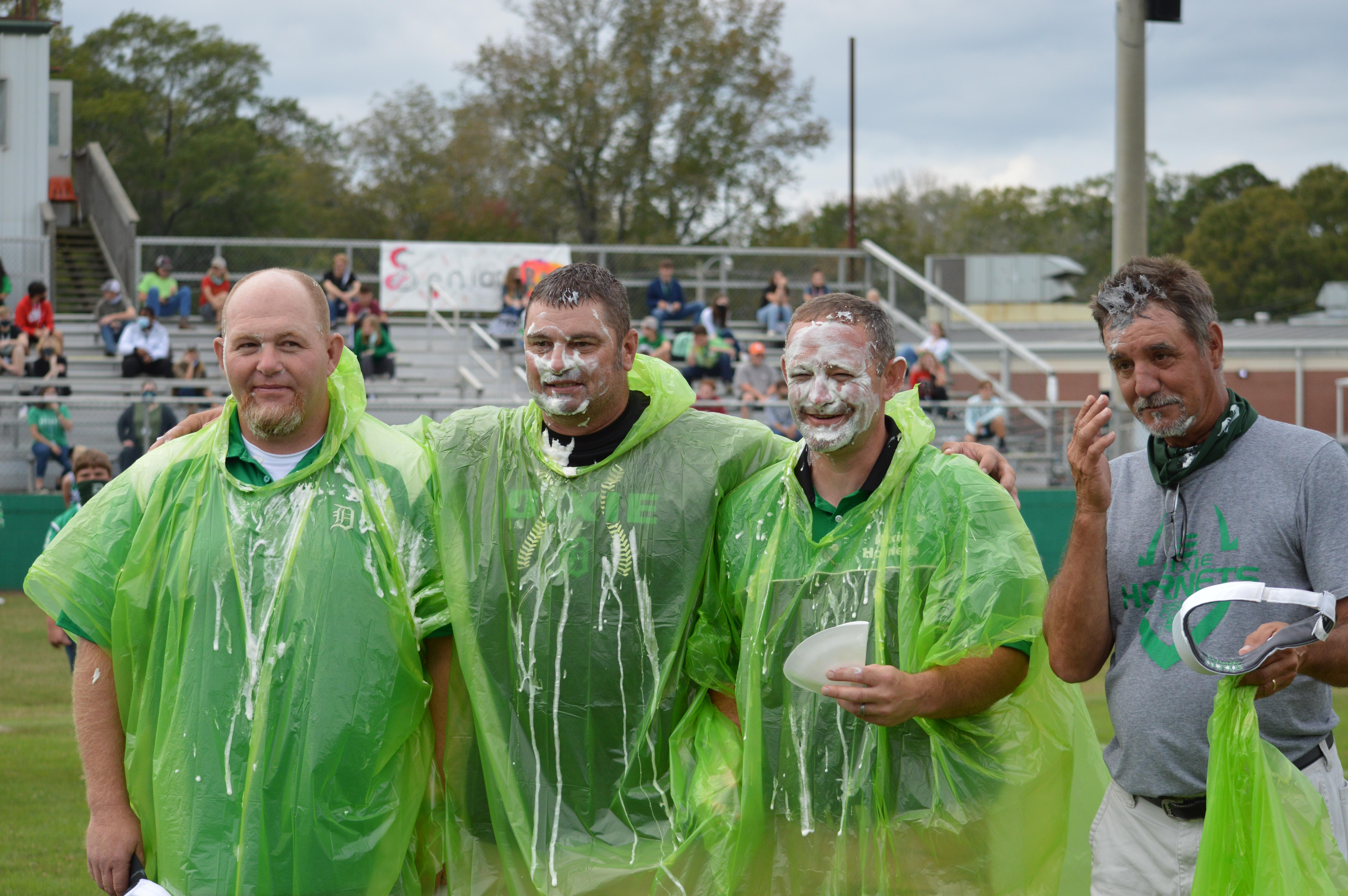 Coaches pose after having pie thrown in their faces.