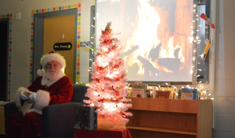 Santa Claus speaking to children with Christmas tree lit up next to him.
