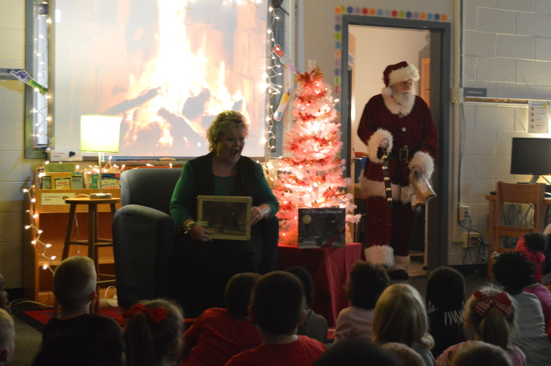 Teacher reading book with Santa Claus in background