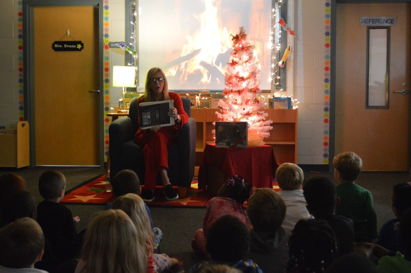 Teacher reads The Polar Express book to students with lights out and Christmas tree illuminated in the background