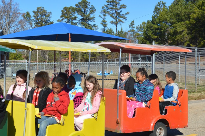 Students riding trolley outside on playground