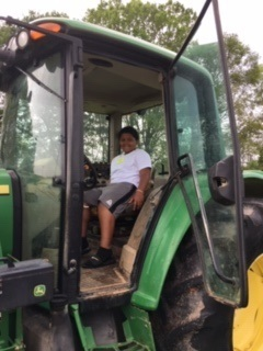 student sits inside large tractor